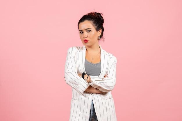 Vista frontal jovem com jaqueta branca posando em um fundo rosa claro senhora cor da moda mulher emoção