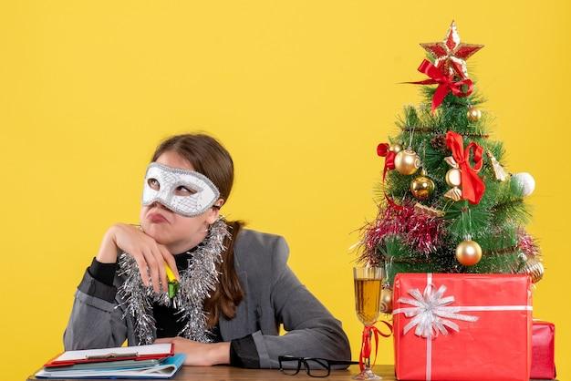 Vista frontal, jovem com máscara de baile de máscaras sentada à mesa árvore de natal e coquetel