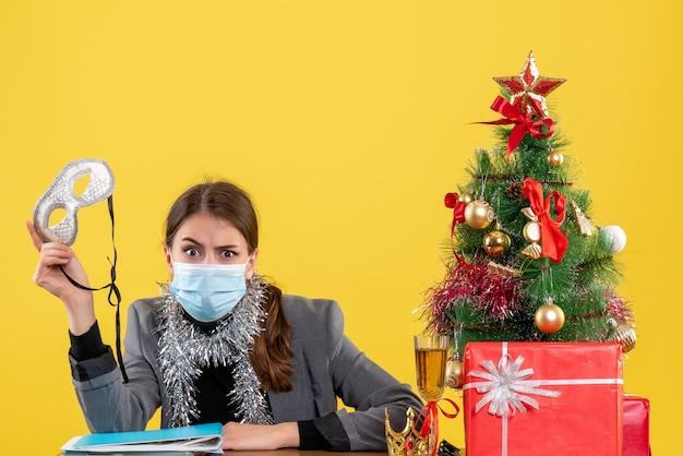 Vista frontal jovem com máscara médica sentada à mesa segurando máscara de baile de máscaras, árvore de natal e coquetel de presentes
