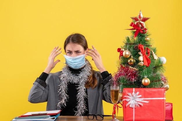 Vista frontal jovem com máscara médica sentada à mesa tirando a máscara árvore de natal e coquetel de presentes