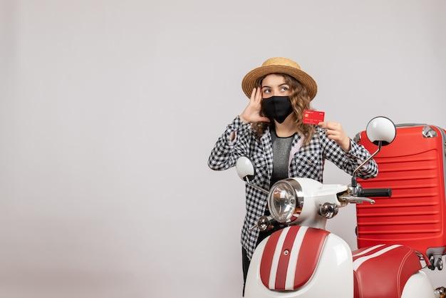 Vista frontal jovem com máscara preta segurando o bilhete em pé perto da motocicleta vermelha