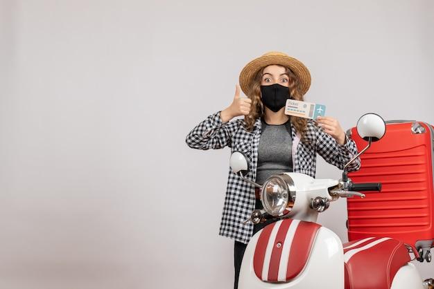 Vista frontal jovem com máscara preta segurando o tíquete e fazendo sinal de positivo em pé perto da motocicleta vermelha