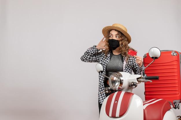 Vista frontal jovem com máscara preta segurando um cartão, ouvindo algo em pé perto de motocicleta vermelha