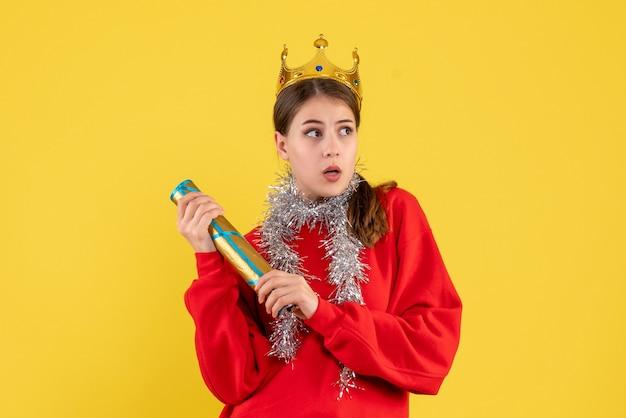 Vista frontal jovem com suéter vermelho e coroa segurando um popper de festa