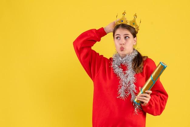 Vista frontal jovem com suéter vermelho segurando um popper de festa e sua coroa