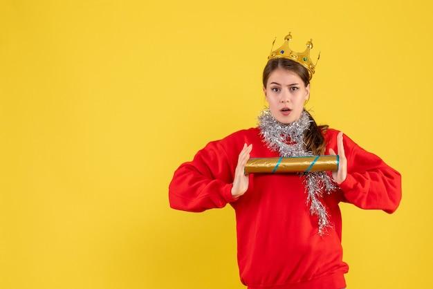 Vista frontal jovem com suéter vermelho segurando uma pipoca