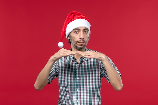Vista frontal jovem com tampa de ano novo na parede vermelha homem vermelho feriados de ano novo