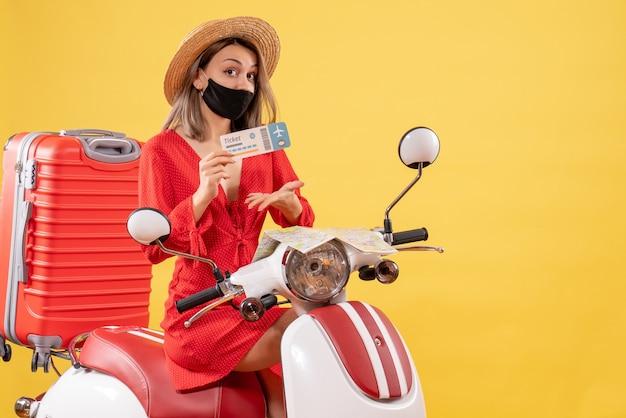 Vista frontal jovem com vestido vermelho e chapéu panamá na motocicleta segurando o ingresso