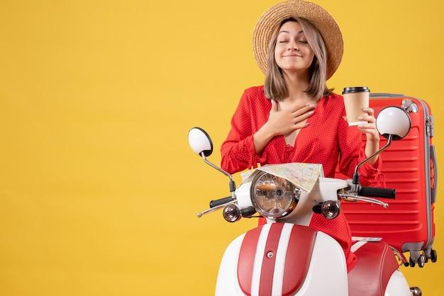 Vista frontal jovem com vestido vermelho fechando os olhos segurando uma xícara de café perto de um ciclomotor