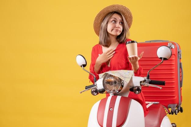 Vista frontal jovem com vestido vermelho segurando a xícara de café e colocando a mão no queixo perto da motocicleta