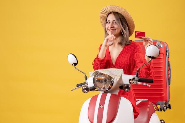 Vista frontal jovem com vestido vermelho segurando um cartão do banco, fazendo sinal de shh na motocicleta