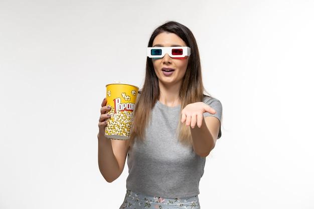 Vista frontal jovem comendo pipoca e assistindo filme com óculos de sol d na superfície branca