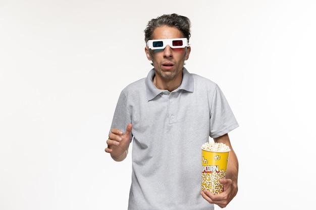 Vista frontal jovem comendo pipoca em óculos de sol d em um chão branco filme de homem remoto