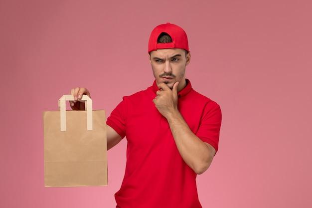 Vista frontal jovem correio masculino com capa uniforme vermelha, segurando o pacote de comida de papel com a expressão do pensamento no fundo rosa.