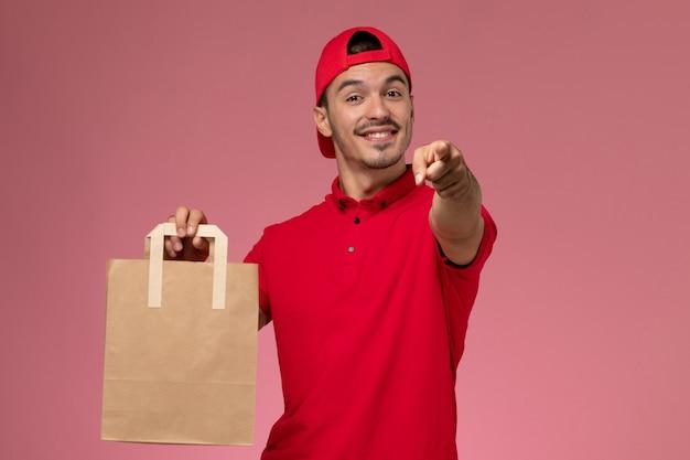 Vista frontal jovem correio masculino com capa uniforme vermelha, segurando o pacote de comida de papel e sorrindo no fundo rosa.