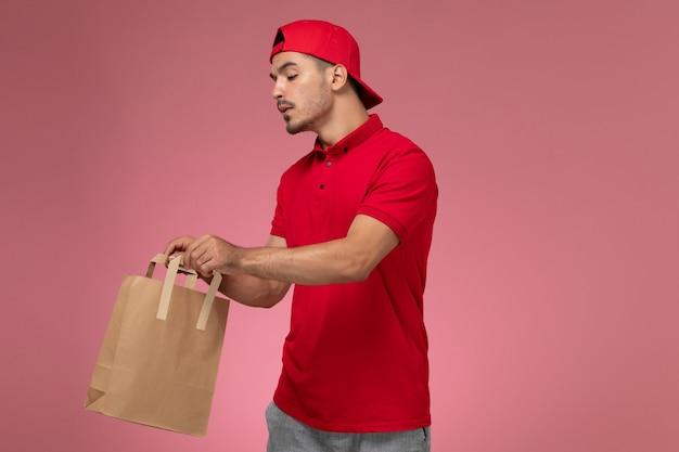 Vista frontal jovem correio masculino com capa uniforme vermelha, segurando o pacote de comida de papel na mesa rosa.