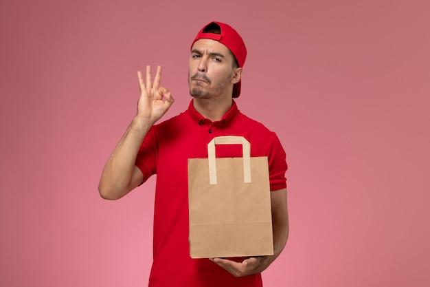 Vista frontal jovem correio masculino com capa uniforme vermelha, segurando o pacote de comida de papel no fundo rosa.