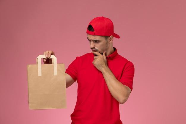 Vista frontal jovem correio masculino com capa uniforme vermelha, segurando o pensamento de pacote de comida de papel sobre o fundo rosa claro.
