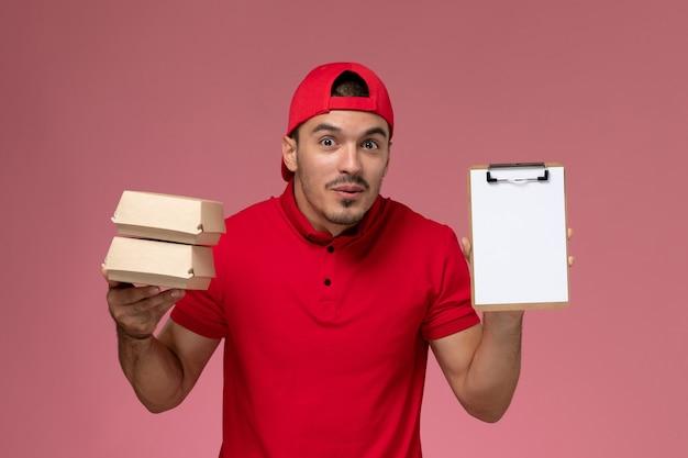 Vista frontal jovem correio masculino com capa uniforme vermelha segurando pequenos pacotes com comida e o bloco de notas sobre fundo rosa claro.