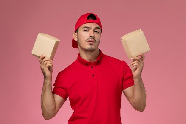 Vista frontal jovem correio masculino com capa uniforme vermelha segurando pequenos pacotes com comida no fundo rosa.