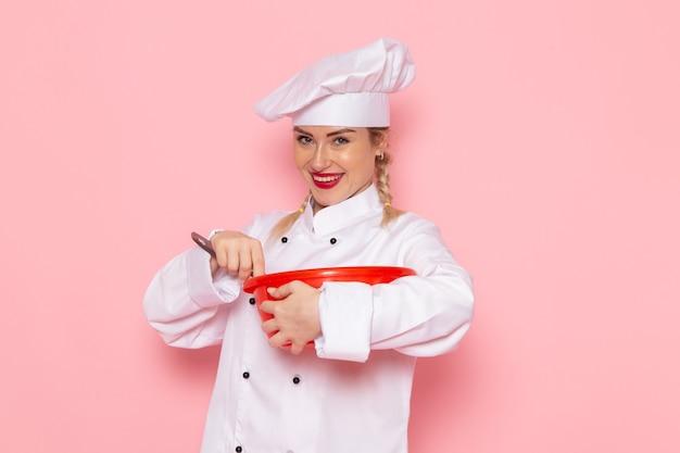 Vista frontal jovem cozinheira em terno branco, misturando a tigela vermelha no espaço rosa.