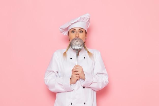 Vista frontal jovem cozinheira em terno branco, posando com uma colher de prata no espaço rosa.