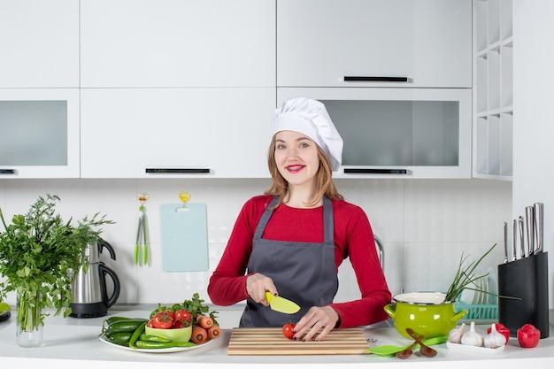Vista frontal jovem cozinheira no chapéu de cozinheira cortando tomate