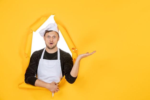 Vista frontal jovem cozinheiro masculino com capa branca e boné amarelo rasgado fundo comida trabalho branco cozinha homem cozinha foto cor