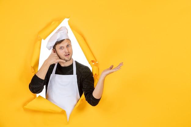Vista frontal jovem cozinheiro masculino com capa branca e boné em um fundo amarelo rasgado trabalho de comida homem branco cozinha foto cor cozinha
