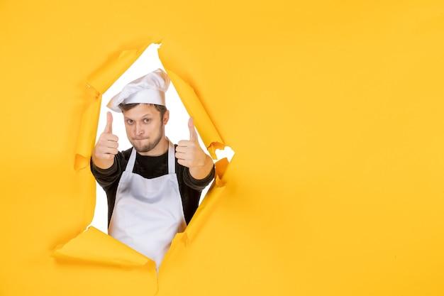 Vista frontal jovem cozinheiro masculino com capa branca e boné encantado com fundo amarelo comida homem branco cozinha foto cor cozinha