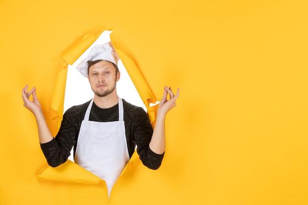 Vista frontal jovem cozinheiro masculino com capa branca e boné meditando sobre fundo amarelo comida homem branco cozinha foto cozinha cor