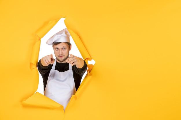 Vista frontal jovem cozinheiro masculino com capa branca e boné no fundo amarelo comida homem branco cozinha foto cores cozinha