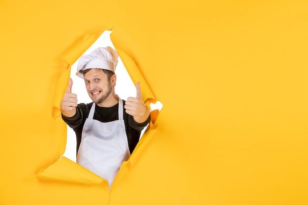Vista frontal jovem cozinheiro masculino com capa branca e boné tentando sorrir no fundo amarelo comida homem branco cozinha foto cozinha cor