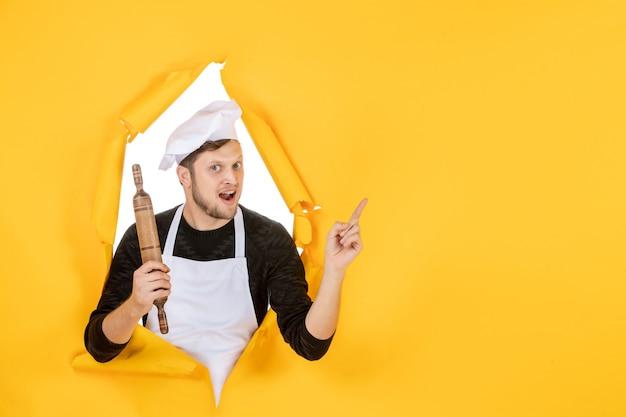 Vista frontal jovem cozinheiro masculino com capa branca segurando o rolo de massa no fundo amarelo comida homem branco foto cor trabalho de cozinha