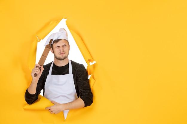 Vista frontal jovem cozinheiro masculino com capa branca segurando o rolo de massa no fundo amarelo foto comida cozinha cozinha trabalho cor branca