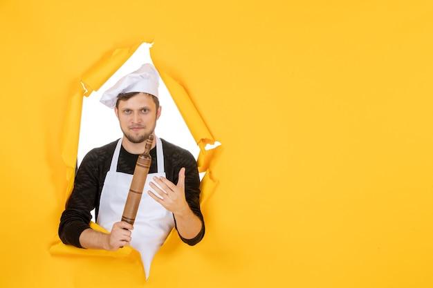 Vista frontal jovem cozinheiro masculino com capa branca segurando o rolo de massa no fundo amarelo foto comida homem cozinha cozinha trabalho cor branca