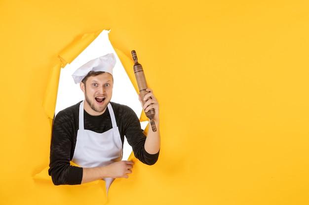 Vista frontal jovem cozinheiro masculino com capa branca segurando o rolo de massa sobre um fundo amarelo comida homem branco cozinha foto cor trabalho de cozinha