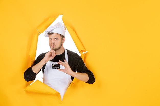 Vista frontal jovem cozinheiro masculino com capa branca segurando um cartão do banco preto no fundo amarelo modelo cor branca cozinha trabalho homem comida dinheiro