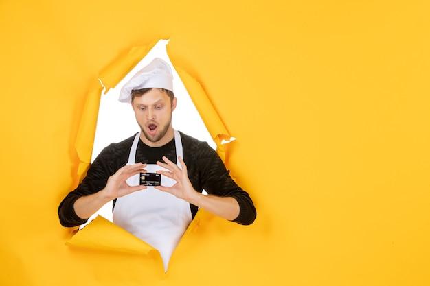 Vista frontal jovem cozinheiro masculino com capa branca segurando um cartão do banco preto sobre fundo amarelo branco cor culinária homem comida dinheiro