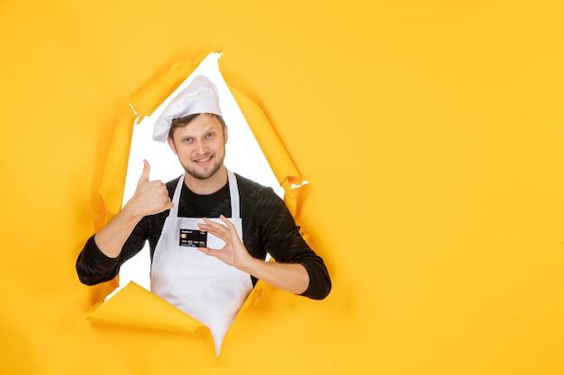 Vista frontal jovem cozinheiro masculino com capa branca segurando um cartão do banco preto sobre fundo amarelo modelo cor branca trabalho homem comida dinheiro