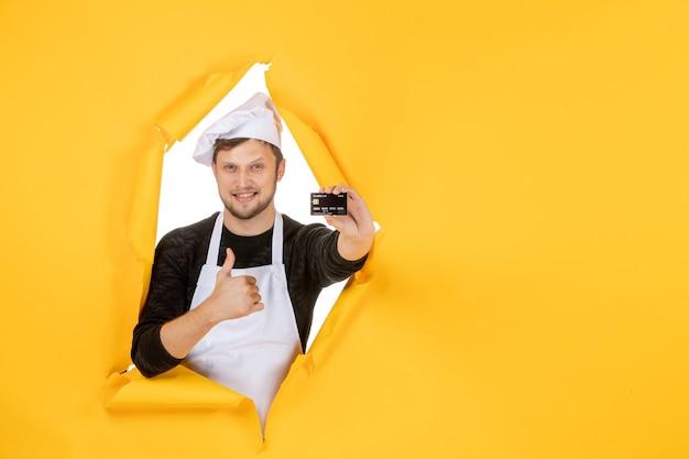Vista frontal jovem cozinheiro masculino com capa branca segurando um cartão do banco preto sobre um fundo amarelo branco cor cozinha trabalho homem comida cozinha