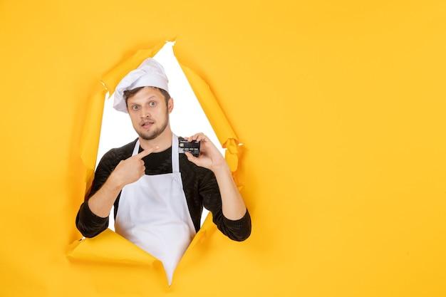 Vista frontal jovem cozinheiro masculino com capa branca segurando um cartão do banco preto sobre um fundo amarelo branco cor cozinha trabalho homem comida dinheiro