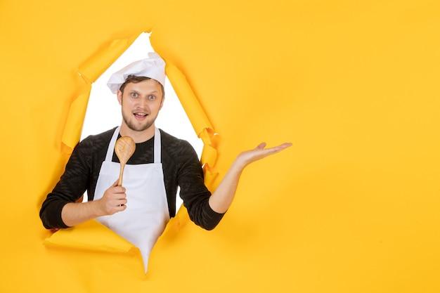 Vista frontal jovem cozinheiro masculino com capa branca segurando uma colher de pau no fundo amarelo cor cozinha foto cozinha trabalho branco comida