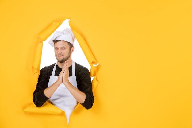 Vista frontal jovem cozinheiro masculino em capa branca e boné em fundo amarelo comida homem branco cozinha foto cor cozinha trabalho