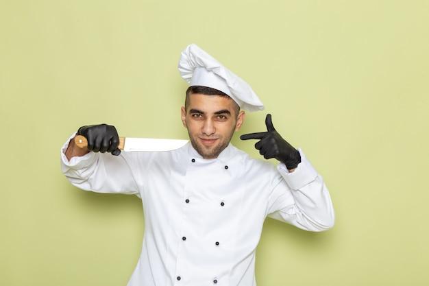 Vista frontal jovem cozinheiro masculino em terno branco de cozinheiro usando luvas escuras e segurando uma faca na cor verde