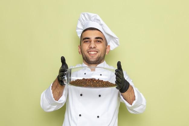 Vista frontal jovem cozinheiro masculino em terno branco, sorrindo e segurando um copo com sementes de café no verde