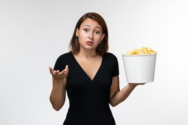 Vista frontal jovem de camisa preta segurando batatas fritas na superfície branca