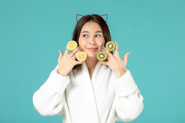Vista frontal jovem de roupão segurando fatias de limão e kiwis no fundo azul