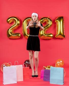 Vista frontal jovem de vestido preto abrindo bolsas de mãos em balões no chão vermelho