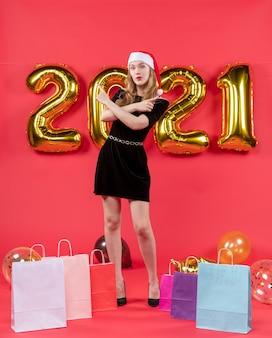 Vista frontal jovem de vestido preto apontando para algo cruzando as mãos de uma sacola em balões no chão em vermelho